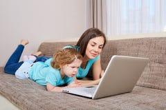 Bemuttern Sie und ihre Tochter, die zu Hause Laptop betrachtet stockbild