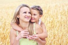 Bemuttern Sie und ihre Tochter am Weizenfeld lizenzfreies stockfoto