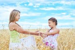 Bemuttern Sie und ihre Tochter am Weizenfeld lizenzfreie stockbilder