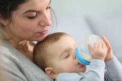Bemuttern Sie und ihre Trinkmilchform des Babys eine Babyflasche Stockfotografie
