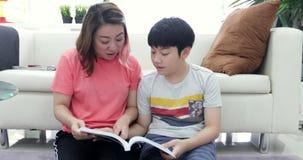 Bemuttern Sie und sein Sohnlesebildungsbuch, die Mutter, die seinem Sohn hilft, der Ihre Hausarbeit tut stock footage