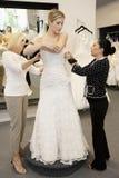 Bemuttern Sie und speichern Sie den Angestellten, der die junge Frau unterstützt, die im Brautspeicher angekleidet erhält stockbilder