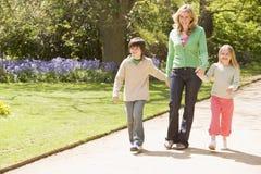 Bemuttern Sie und zwei junge Kinder, die auf Pfad gehen Lizenzfreie Stockfotografie