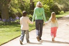 Bemuttern Sie und zwei junge Kinder, die auf Pfad gehen Stockfotografie