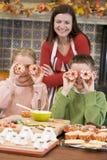 Bemuttern Sie und zwei Kinder bei Halloween in der Küche Lizenzfreies Stockfoto