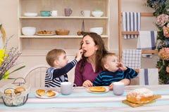 Bemuttern Sie und zwei Kinder in der Küche, die frühstückt Lizenzfreie Stockfotografie