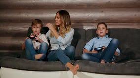 Bemuttern Sie und zwei Söhne, die auf dem Sofa in seinem Haus sitzen, das Videospiele mit drahtlosem Steuerknüppel spielt Glückli