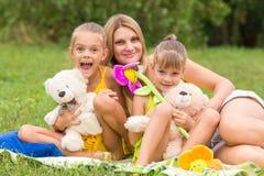 Bemuttern Sie und zwei Töchter, die mit weichen Spielwaren auf einem Picknick sitzen lizenzfreie stockfotos