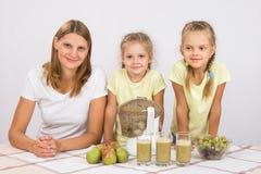 Bemuttern Sie und zwei Töchter, um für drei Gläser von Saft Juicer zu kochen stockfotografie