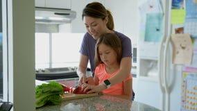 Bemuttern Sie unterrichtende Tochter, um Gemüse in der Küche 4k zu hacken stock video