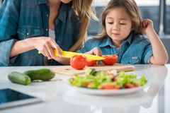 Bemuttern Sie unterrichtendes Mädchen, wie man einen Salat macht stockbild