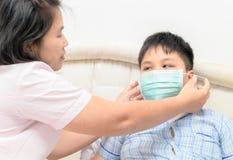 Bemuttern Sie Verschleißschutzmaskensohn, um sich gegen Grippe Vir zu schützen Lizenzfreies Stockfoto