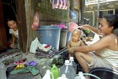Bemuttern Sie waschendes Kind in Elendsviertel apfelsaurem Salz, Philippinen Lizenzfreies Stockbild