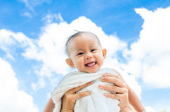 Bemuttern Sie werfen oben Babytochter mit Tuch auf Hintergrund des blauen Himmels Lizenzfreies Stockfoto