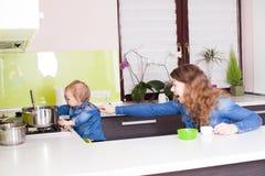 Bemuttern Sie worns Baby von der Gefahr in der Küche stockfoto
