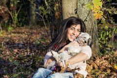 Benägenhet för ung kvinna på ett höstträd som kramar hennes hund royaltyfri foto