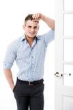 Benägenhet för ung man för stående tillfällig mot ramen av en öppen dörr på ljus bakgrund som ler och ser till kameran Royaltyfri Fotografi
