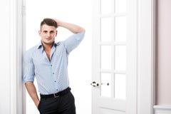 Benägenhet för ung man för stående tillfällig mot ramen av en öppen dörr på ljus bakgrund som ler och ser till kameran Arkivbilder