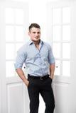 Benägenhet för ung man för stående tillfällig mot ramen av en öppen dörr på ljus bakgrund som ler och ser till kameran Royaltyfri Foto