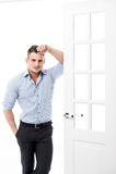 Benägenhet för ung man för stående tillfällig mot ramen av en öppen dörr på ljus bakgrund som ler och ser till kameran Arkivfoto