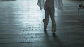 Ben av ballerina på tårna och i hoppet Flickadanserna på en trägolvsnurr på axeln på ett ben lager videofilmer