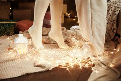 Ben av barn kopplar ihop i den mörka träinre med ljus, stearinljuslykta svarta par för bakgrund som kramar manromantikerkvinnan F Royaltyfri Foto