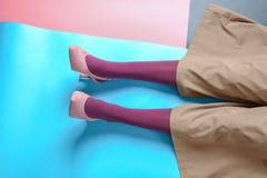 Ben av den unga kvinnan i strumpbyxor och byxa på färgbakgrund arkivbilder