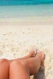 Ben av den unga kvinnan på stranden Arkivfoto