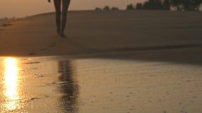Ben av den unga kvinnan som g?r vidare havet, s?tter p? land under soluppg?ng Kvinnlig fot som barfota g?r p? havskust p? solnedg stock video