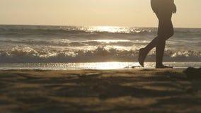 Ben av den unga kvinnan som kliver på sand Stäng sig upp av kvinnlig fot som går på guld- sand på stranden med havvågor på lager videofilmer
