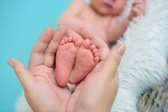 Ben av det nyfött behandla som ett barn i moderns händer royaltyfria bilder