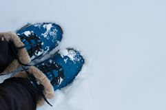 Ben av en flicka i kängor i en snödriva Arkivbild
