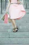 Ben av en flicka med shopping i en klänning royaltyfri foto