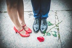 Ben av en man i svarta skor och kvinnor i röda skor Romantiker co Arkivbilder