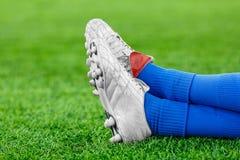 Ben av en spelare i fotboll på en grön gräsmatta royaltyfri bild