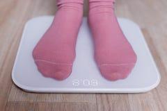 Ben av en ung kvinna som mäter hennes vikt på modern smart våg arkivfoto