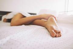 Ben av en ung kvinnlig som sover i säng royaltyfri fotografi