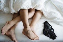 Ben av ett par som sover i säng arkivbild