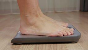 Ben av konditionkvinnor som kliver till att väga skalan för kroppmass, kontrollerar tätt upp lager videofilmer