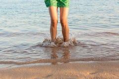 Ben av kvinnan som kör på stranden med att plaska för vatten för sommarterritorium för katya krasnodar semester ben av en flicka  arkivbild