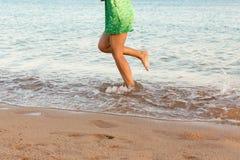 Ben av kvinnan som k?r p? stranden med att plaska f?r vatten f?r sommarterritorium f?r katya krasnodar semester ben av en flicka  royaltyfria foton