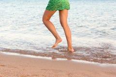 Ben av kvinnan som k?r p? stranden med att plaska f?r vatten f?r sommarterritorium f?r katya krasnodar semester ben av en flicka  arkivbild