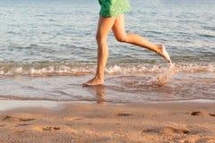 Ben av kvinnan som k?r p? stranden med att plaska f?r vatten f?r sommarterritorium f?r katya krasnodar semester ben av en flicka  arkivfoto