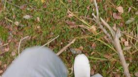 Ben av mannen i vita gummikängor som går i höstskog stock video