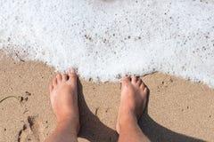 Ben av personen på en sand Ben av ett mananseende på sandjonen stranden från över Horisontaldet friaskott _ Arkivbild