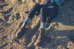 Ben av sammanträde för ung kvinna på stranden Arkivfoto