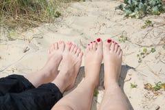 Ben av två kvinnor som solbadar på stranden Arkivfoto