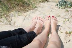 Ben av två kvinnor som solbadar på stranden Royaltyfri Bild