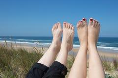 Ben av två kvinnor som solbadar på stranden Arkivbild