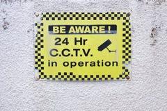 Ben bewuste 24 u-de veiligheidscamera van uurkabeltelevisie in verrichtings geel teken op witte muur Stock Afbeeldingen